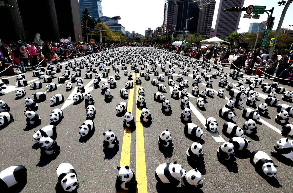 "Papier mache pandas, created by French Paolo Grangeon, are seen displayed outside the Taipei City Hall as part of an exhibition called ""Pandas on Tour"""